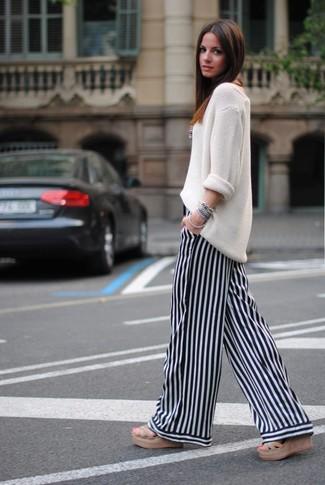 Comment porter: pull surdimensionné en tricot blanc, pantalon large à rayures verticales blanc et noir, sandales tressées marron clair, bracelet bleu