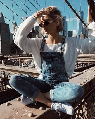 Comment porter: pull surdimensionné blanc, salopette en denim bleue, chaussures de sport blanches, lunettes de soleil marron foncé
