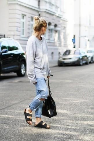 Comment porter: pull surdimensionné gris, jean boyfriend déchiré bleu clair, sandales plates en cuir noires, sac fourre-tout en cuir noir