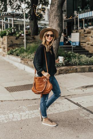 Comment porter: pull surdimensionné noir, jean skinny déchiré bleu, baskets basses en daim beiges, sac fourre-tout en cuir tabac