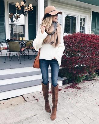 Comment porter des bottes hauteur genou en daim marron: Marie un pull surdimensionné en tricot blanc avec un jean skinny bleu marine pour un look idéal le week-end. Apportez une touche d'élégance à votre tenue avec une paire de bottes hauteur genou en daim marron.