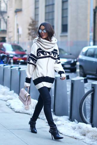 Comment porter: pull surdimensionné imprimé blanc et noir, jean skinny noir, bottines en cuir noires, cartable en cuir rose