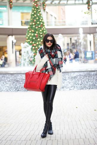 Choisis pour le confort dans un pull surdimensionné en tricot blanc et des leggings en cuir noirs. Une paire de des bottines en cuir noires ajoutera de l'élégance à un look simple.