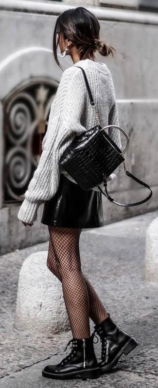 Comment porter: pull surdimensionné en tricot gris, minijupe en cuir noire, bottines plates à lacets en cuir noires, sac à dos en cuir matelassé noir