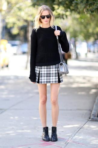 Comment porter: pull surdimensionné noir, minijupe écossaise noire et blanche, bottines plates à lacets en cuir noires, sac bandoulière en cuir argenté