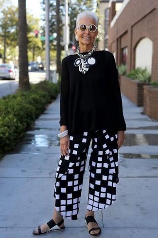 Comment porter: pull surdimensionné noir, pantalon large à carreaux noir et blanc, sandales plates en cuir noires, lunettes de soleil blanches