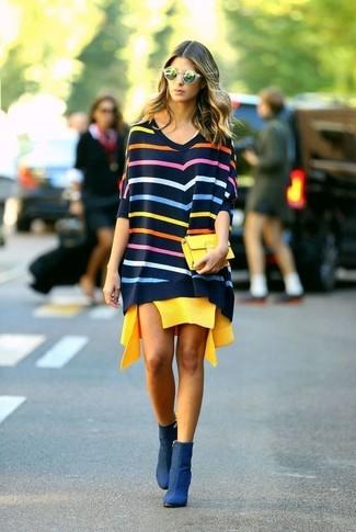 Comment porter: pull surdimensionné à rayures horizontales multicolore, robe décontractée jaune, bottines en nubuck bleu marine, pochette jaune