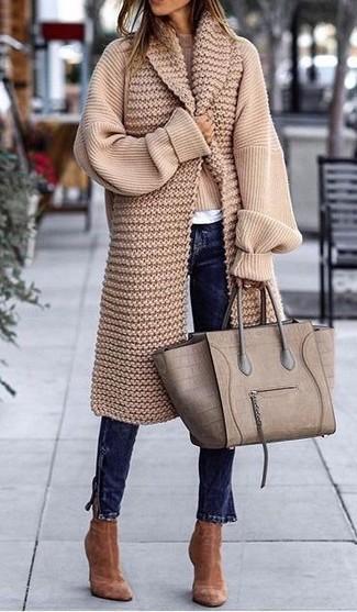 Comment porter: pull surdimensionné en tricot beige, t-shirt à col rond blanc, jean skinny bleu marine, bottines en daim marron