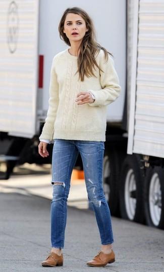 Comment porter: pull torsadé beige, t-shirt à manche longue blanc, jean skinny déchiré bleu, chaussures richelieu en cuir marron clair