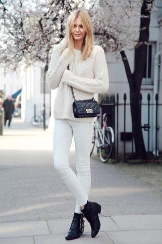 Comment porter un jean skinny blanc: Essaie de marier un pull torsadé blanc avec un jean skinny blanc pour un look de tous les jours facile à porter. Complète ce look avec une paire de des bottines en cuir noires.
