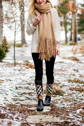 Comment porter: pull torsadé blanc, leggings noirs, bottes de pluie écossaises noires, écharpe marron clair