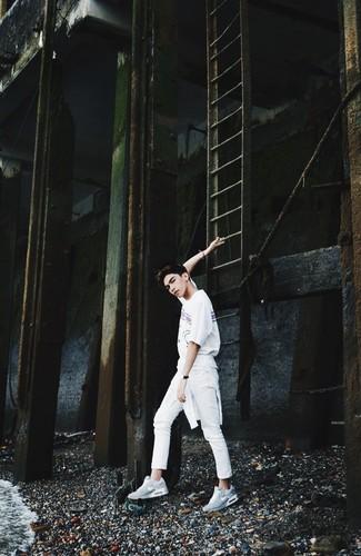Comment porter: pull torsadé blanc, t-shirt à col rond imprimé blanc, pantalon chino blanc, chaussures de sport grises