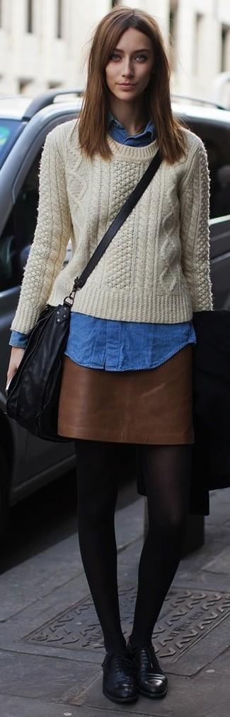 Comment porter: pull torsadé beige, chemise en jean bleue, minijupe en cuir marron, chaussures richelieu en cuir noires