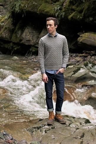Comment porter: pull torsadé gris, chemise à manches longues en chambray bleue, jean bleu marine, bottes d'hiver marron clair