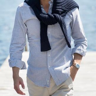 Comment porter: pull torsadé noir, chemise à manches longues à rayures verticales blanc et bleu, pantalon chino beige