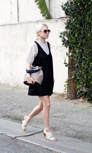 Comment porter: robe chasuble noire, t-shirt à col en v blanc, sandales compensées en cuir blanches, sac bourse en toile à carreaux beige