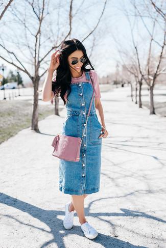 Comment porter: robe chasuble en denim bleue, t-shirt à col rond rose, baskets basses en toile blanches, sac bandoulière en cuir rose
