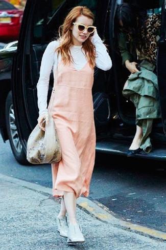 Comment porter: robe chasuble rose, t-shirt à manche longue blanc, bottines en cuir grises, sac bourse à fleurs beige
