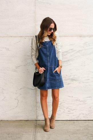 Comment porter: robe chasuble en denim bleu marine, t-shirt à manche longue à rayures horizontales blanc et noir, bottines en daim marron clair, sac bandoulière en cuir noir