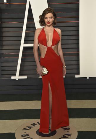 Tenue de Miranda Kerr: Robe de soirée découpée rouge, Sandales à talons en cuir dorées, Pochette dorée, Bracelet doré