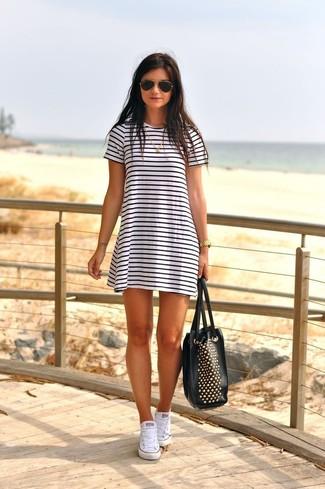 Comment porter: robe décontractée à rayures horizontales blanche et noire, baskets montantes en toile blanches, sac fourre-tout en cuir à clous noir et doré, lunettes de soleil noir et doré