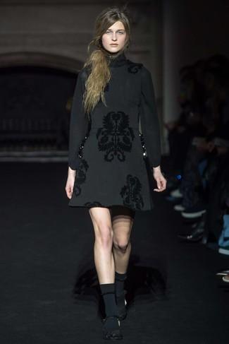 Opte pour une robe fourreau en brocart noire pour un ensemble de bureau stylé. Cette tenue est parfait avec une paire de des escarpins en dentelle noirs.