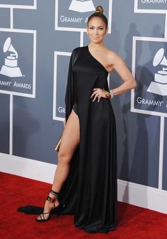 Tenue de Jennifer Lopez: Robe longue fendue noire, Sandales à talons en cuir noir et doré, Pochette dorée, Bracelet doré