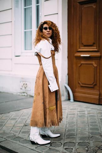 Comment porter des bottes western en cuir blanches: Une robe midi en daim marron clair et une chemise de ville blanche sont l'association de ce que chaque fille stylée devrait avoir dans sa garde-robe. Si tu veux éviter un look trop formel, fais d'une paire de des bottes western en cuir blanches ton choix de souliers.