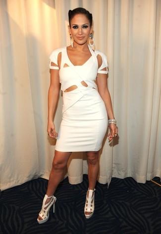 Tenue de Jennifer Lopez: Robe moulante découpée blanche, Sandales à talons en cuir blanches, Bracelet argenté, Boucles d'oreilles argentées