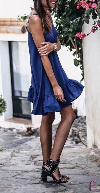 Comment porter: robe trapèze bleu marine, sandales à talons en cuir à clous noires, bracelet doré