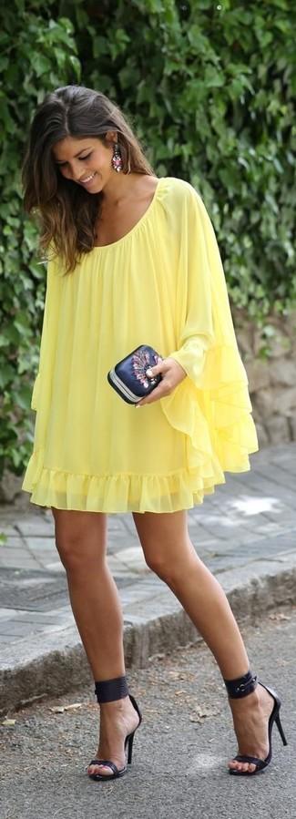 Porte une robe trapèze jaune et une pochette en cuir ornée noire pour un déjeuner le dimanche entre amies. Ajoute une paire de des sandales à talons en cuir noires à ton look pour une amélioration instantanée de ton style.