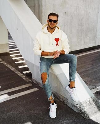 Comment porter: sweat à capuche imprimé blanc, jean skinny déchiré bleu, baskets basses en cuir blanches et noires, lunettes de soleil noires