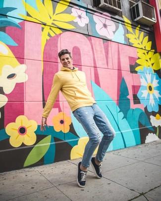 Comment porter: sweat à capuche jaune, jean skinny déchiré bleu clair, baskets basses en toile bleu marine
