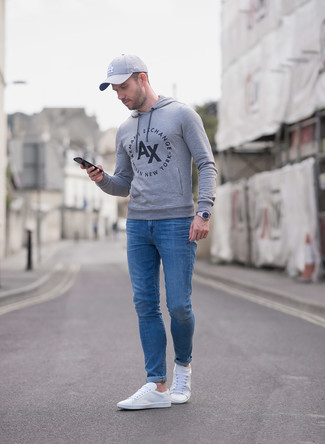 Comment porter: sweat à capuche imprimé gris, jean skinny bleu, baskets basses en toile blanches, casquette de base-ball grise