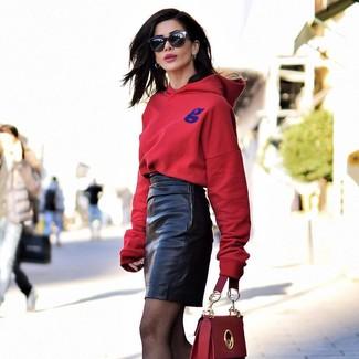 Comment porter: sweat à capuche rouge, minijupe en cuir noire, cartable en cuir rouge, lunettes de soleil noires