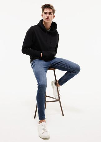 Comment porter: sweat à capuche noir, jean skinny bleu, baskets basses en cuir blanches