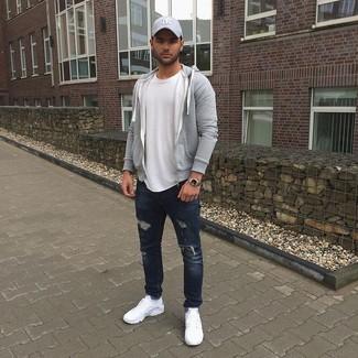 Comment porter: sweat à capuche gris, t-shirt à col rond blanc, jean déchiré bleu marine, chaussures de sport blanches