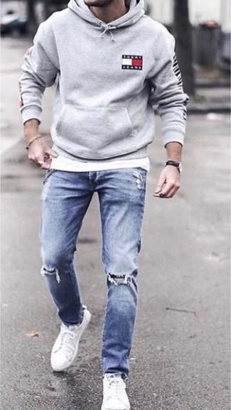 Comment porter: sweat à capuche gris, t-shirt à col rond blanc, jean skinny déchiré bleu, baskets basses en toile blanches