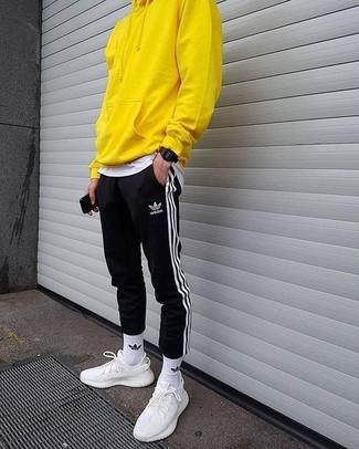 Comment porter: sweat à capuche jaune, t-shirt à col rond blanc, pantalon de jogging à rayures verticales noir et blanc, chaussures de sport blanches