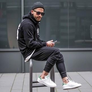 Comment porter: sweat à capuche imprimé noir et blanc, t-shirt à col rond blanc, pantalon de jogging noir, baskets basses en cuir blanches
