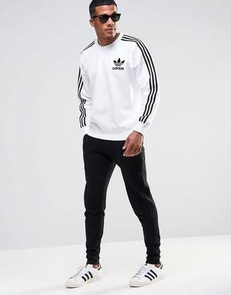 Comment porter: sweat-shirt imprimé blanc et noir, pantalon de jogging noir, baskets basses en cuir blanches et noires, lunettes de soleil noires