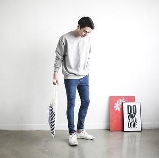 Comment porter un sweat-shirt gris: Essaie d'harmoniser un sweat-shirt gris avec un jean skinny bleu pour un look confortable et décontracté. Assortis ce look avec une paire de des baskets basses en toile blanches.
