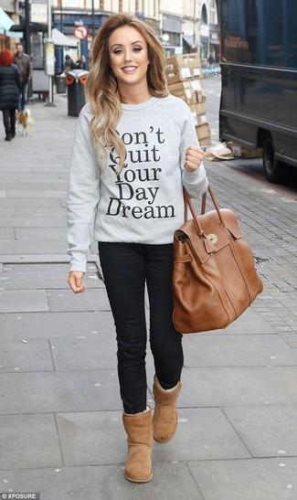 Comment porter: sweat-shirt imprimé gris, jean skinny noir, bottes ugg marron clair, sac fourre-tout en cuir marron