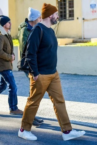 Comment s'habiller après 40 ans: Harmonise un sweat-shirt bleu marine avec un pantalon chino marron clair pour un déjeuner le dimanche entre amis. Cette tenue se complète parfaitement avec une paire de baskets basses en toile blanches.