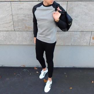 Comment porter: sweat-shirt gris, pantalon de jogging noir, baskets basses en cuir blanches et noires, fourre-tout en cuir noir