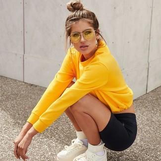 Comment porter: sweat-shirt jaune, short cycliste noir, baskets montantes en cuir blanches, chaussettes blanches