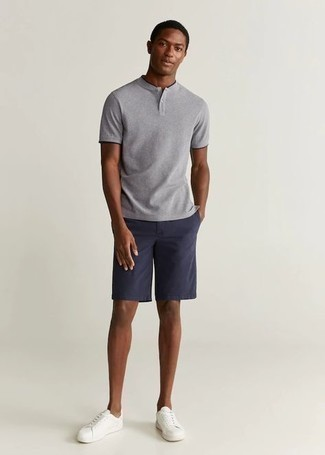 Comment porter un t-shirt à col boutonné gris: Porte un t-shirt à col boutonné gris et un short bleu marine pour un look de tous les jours facile à porter. Une paire de baskets basses en toile blanches est une option judicieux pour complèter cette tenue.