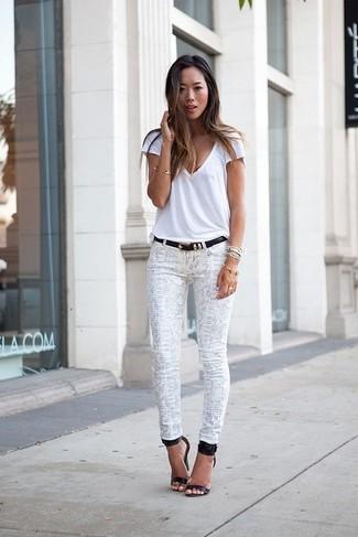 Comment porter: t-shirt à col en v blanc, jean skinny imprimé serpent blanc, sandales à talons en cuir noires, ceinture en cuir noire