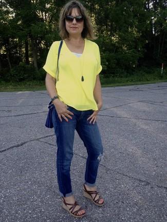 Comment porter: t-shirt à col en v jaune, jean boyfriend déchiré bleu, sandales compensées en cuir marron, sac bandoulière en cuir bleu