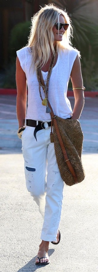 Comment porter: t-shirt à col en v blanc, jean boyfriend déchiré blanc, tongs noires, sac fourre-tout de paille marron